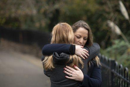 Women-hug-outdoors