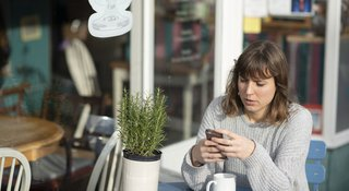 woman-reads-phone-outside