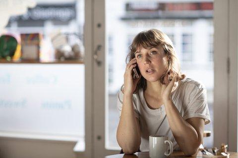 woman-talks-phone-cafe