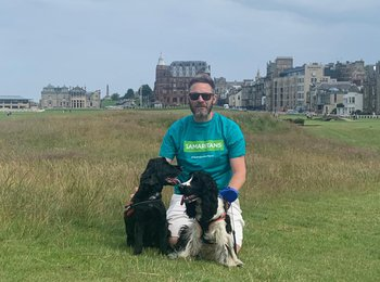 A member of the Phoenix Group's Customer Team wearing a Samaritans t-shirt crouches in a field with his two dogs