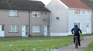 Child on bike outside a row of houses