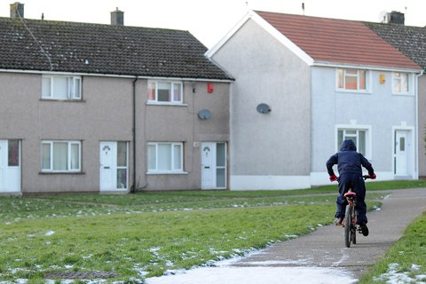 Child on bike outside a row of houses